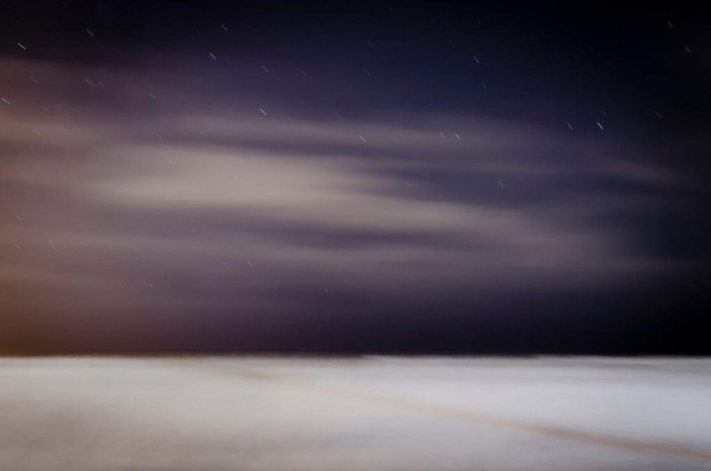 The Pacific Ocean at night with sky, clouds, star trails and distant ship on the horizon.  176 seconds.